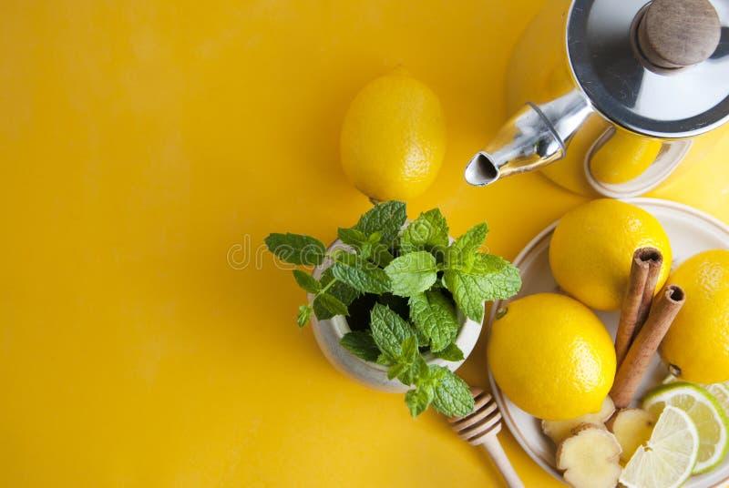 Ingredientes do chá da hortelã fresca: mint, limão no fundo amarelo, vista superior Copie o espaço imagem de stock royalty free