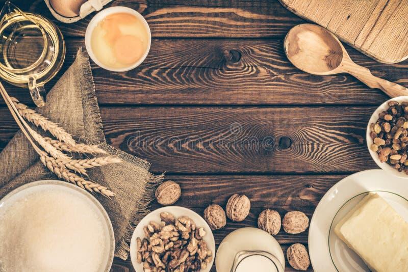 Ingredientes do cozimento para a pastelaria caseiro no fundo de madeira rústico escuro culinar imagem de stock royalty free