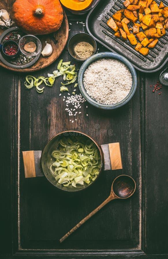 Ingredientes do prato saboroso da abóbora com arroz em cozinhar o potenciômetro no fundo rústico escuro da mesa de cozinha, vista imagens de stock