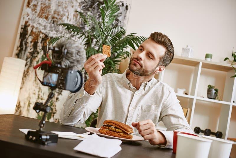 Ingredientes do sanduíche Retrato do blogger farpado masculino que prova um alimento ao gravar o vídeo novo para seu vlog fotografia de stock