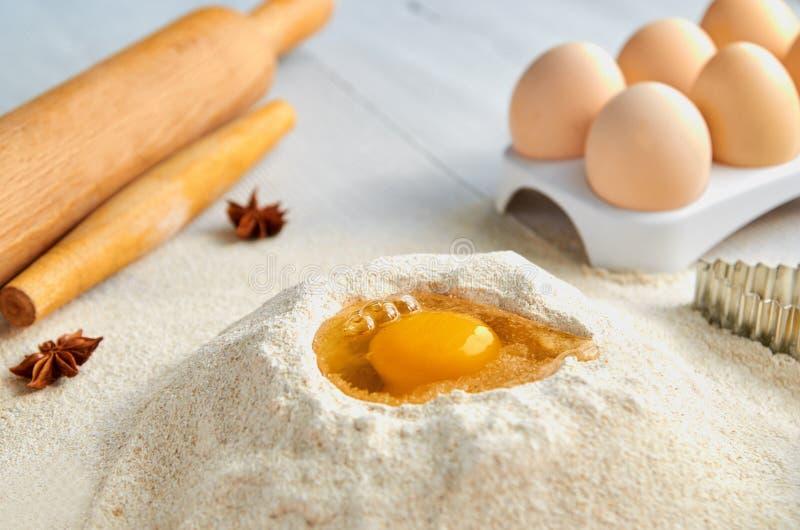 Ingredientes e acessórios da receita da massa na tabela cinzenta: ovos, farinha, especiarias e bakewares Fundo do cozimento fotografia de stock royalty free