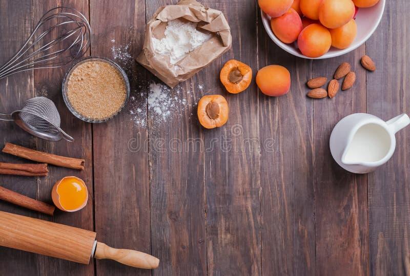 Ingredientes e artigos para fazer uma torta com os abricós no fundo de madeira foto de stock royalty free
