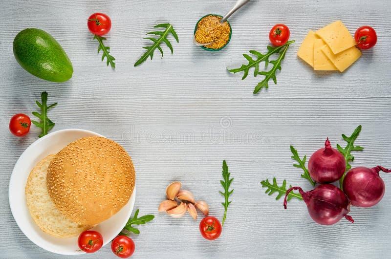 Ingredientes frescos para o hamburguer do vegetariano isolado no fundo concreto cinzento com espaço da cópia gratuita: tomates de fotos de stock