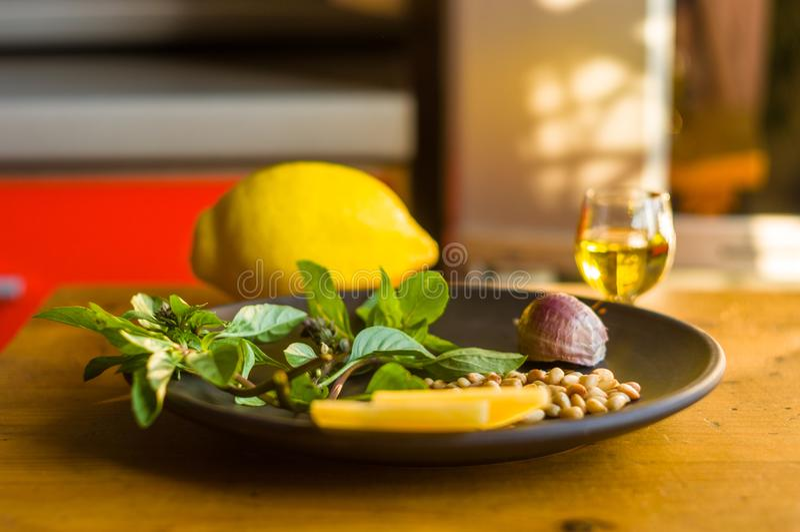 Ingredientes frescos para preparar la salsa italiana del pesto - las puntillas de la albahaca del limón, pelaron las semillas de  fotos de archivo libres de regalías