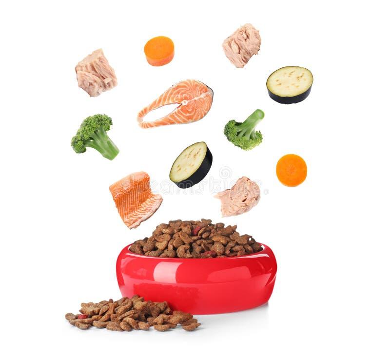 Ingredientes frescos que caen en el cuenco con el alimento para animales seco fotos de archivo