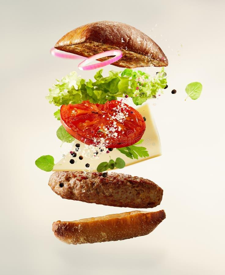 Ingredientes grelhados mergulhados de flutuação do cheeseburger fotos de stock royalty free