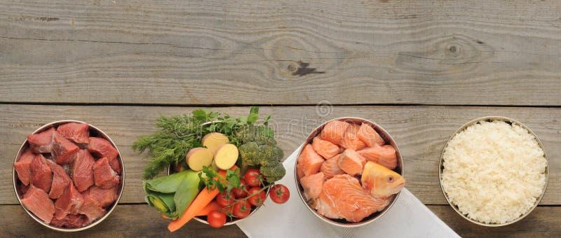 Ingredientes naturales para la comida de perro en cuatro cuencos en el viejo CCB de madera fotografía de archivo libre de regalías