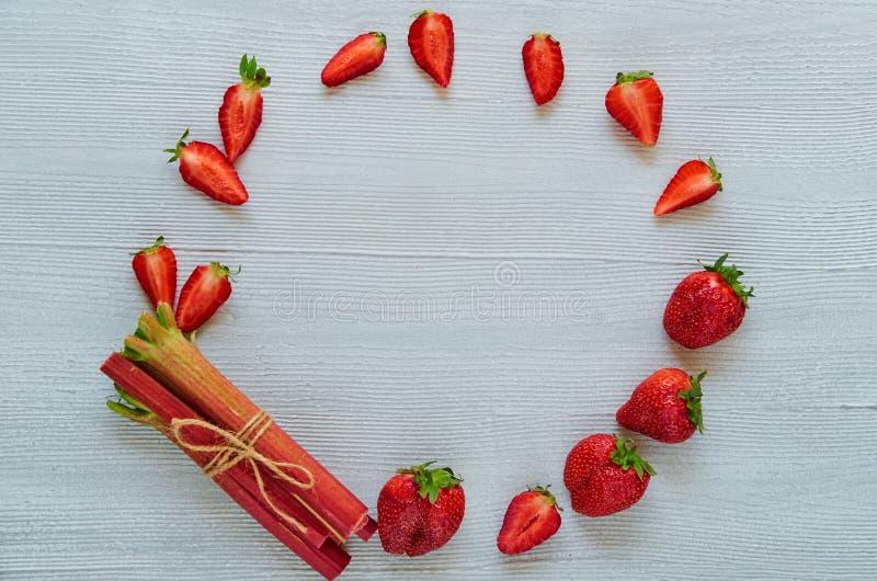Ingredientes orgánicos frescos para cocer la empanada vegetariana o el postre sano - fresas cortadas, ruibarbo crudo del verano e imagenes de archivo