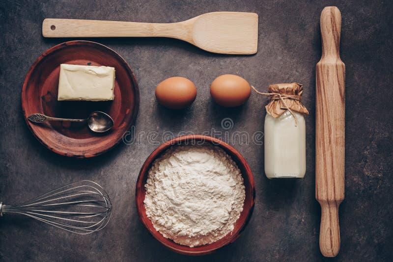 Ingredientes para cocer en un fondo, una harina, una mantequilla, huevos, un rodillo, un batidor y una paleta rústicos oscuros Vi imagenes de archivo