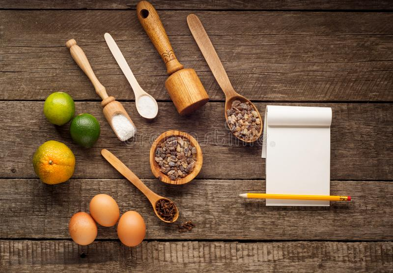 Ingredientes para cocer - harina, azúcar marrón, cal, pimienta inglesa, cuchara de madera, rodillo, huevos Visión superior con el imagen de archivo