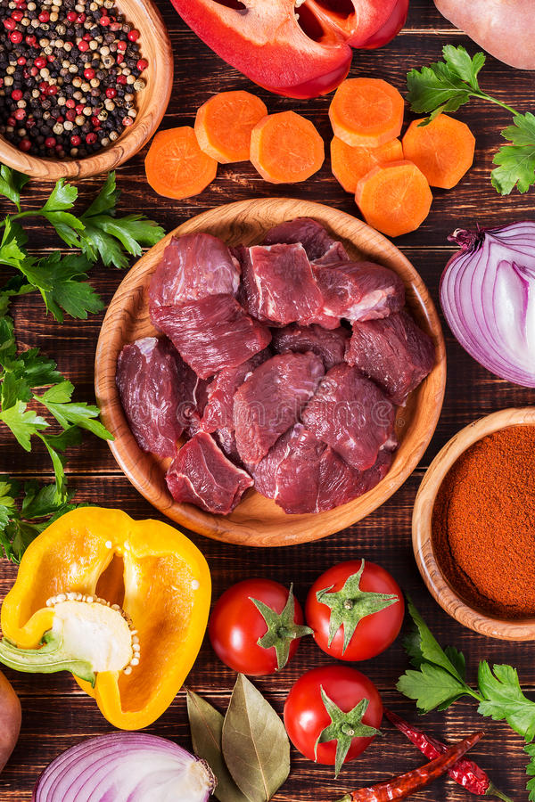 Ingredientes para cocinar del cocido húngaro o del guisado: carne cruda, hierbas, especias, v fotos de archivo