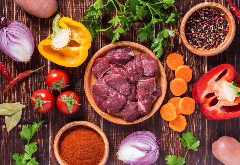 Ingredientes para cocinar del cocido húngaro o del guisado: carne cruda, hierbas, especias, v foto de archivo