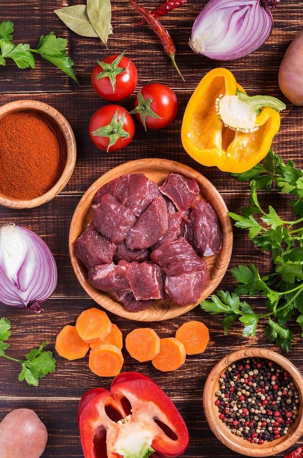 Ingredientes para cocinar del cocido húngaro o del guisado: carne cruda, hierbas, especias, v fotografía de archivo