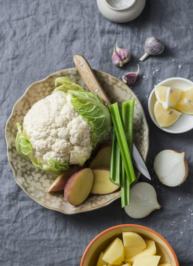 Ingredientes para cocinar el puré en un fondo gris, visión superior de la sopa de la coliflor de la patata Alimento sano vegetari foto de archivo libre de regalías