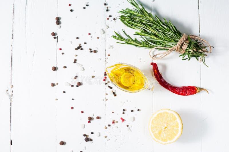 Ingredientes para cocinar Hierbas y romero de las especias Fondo de la comida en la tabla de madera blanca Visión superior fotografía de archivo libre de regalías