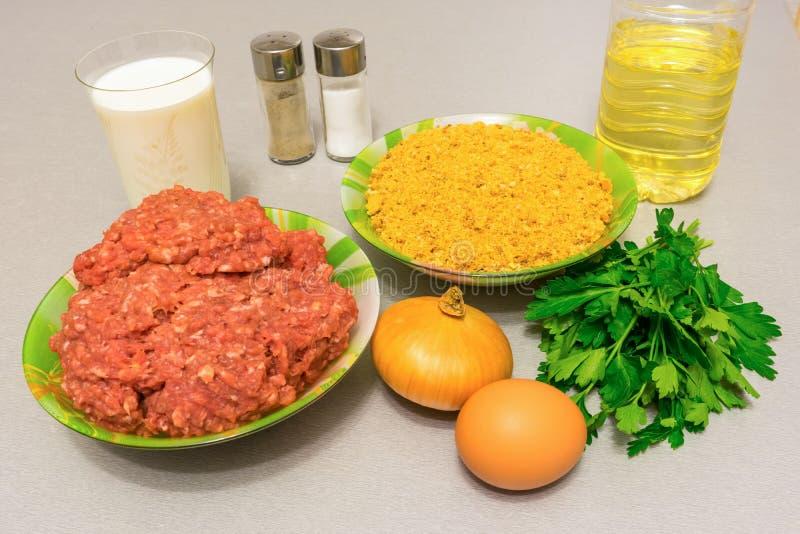 Ingredientes para cocinar las albóndigas: carne picadita, migajas de pan, milipulgada fotografía de archivo