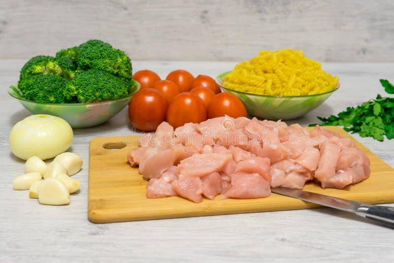 Ingredientes para cocinar las pastas con el pollo y el bróculi que miente encendido imagenes de archivo