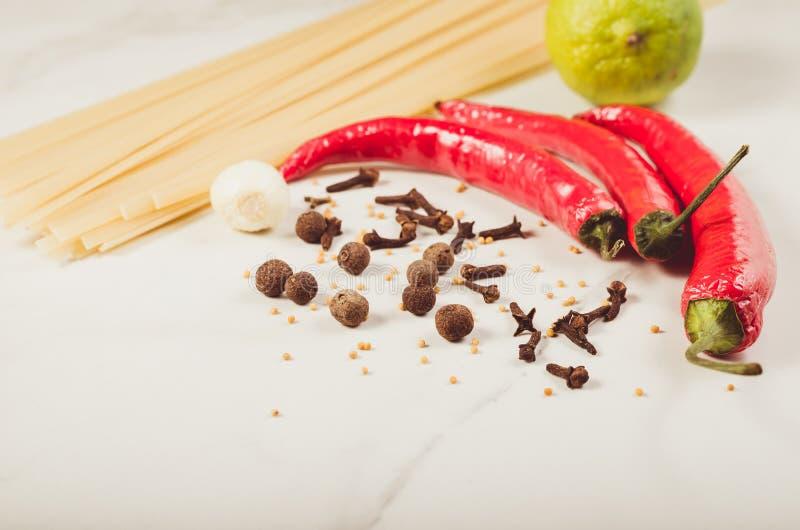 Ingredientes para cocinar los espaguetis/los ingredientes para cocinar los espaguetis en una tabla blanca foto de archivo