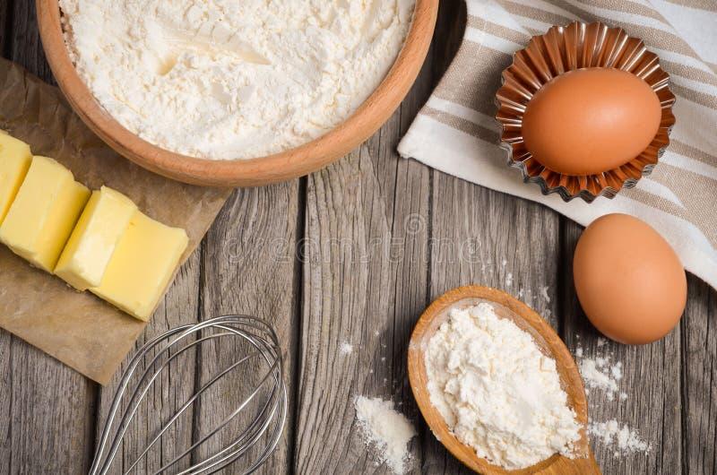 Ingredientes para cozer - leite, manteiga, ovos e farinha Fundo rústico fotografia de stock