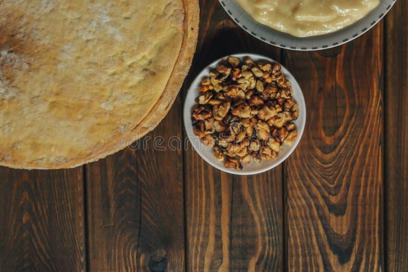 Ingredientes para cozer um bolo, vista superior na placa de madeira shortcakes, buttercream imagem de stock