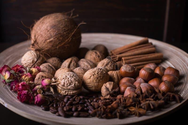 ingredientes para cozer, varas de canela, anis de estrela, cravos-da-índia, porcas, coco, feijões de café em um fundo de madeira imagens de stock