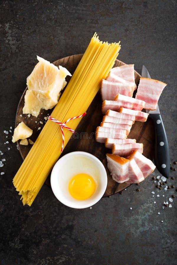 Ingredientes para cozinhar a massa de Carbonara, os espaguetes com pancetta, o ovo e o queijo parmesão duro Culinária italiana tr imagens de stock