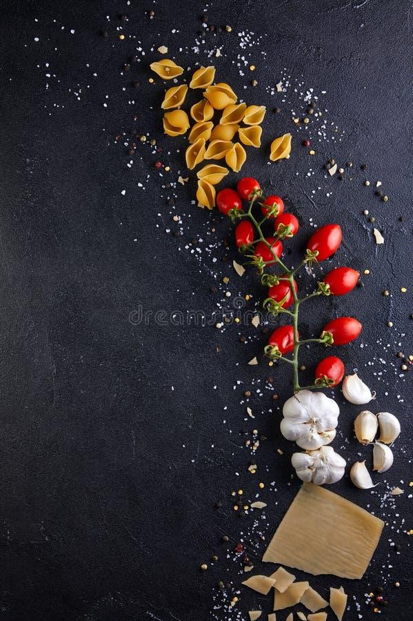 Ingredientes para cozinhar a massa em um fundo preto fotografia de stock