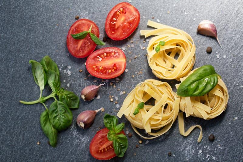 Ingredientes para cozinhar a massa Massa italiana dos tagliatelle com o tomate no fundo de madeira preto imagens de stock