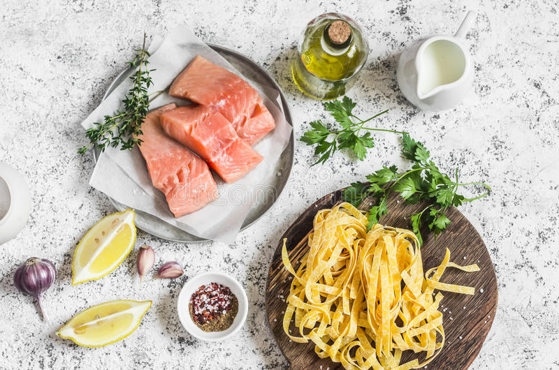 Ingredientes para cozinhar o almoço - salmão cru, tagliatelle secos da massa, creme, azeite, especiarias e ervas Em um fundo clar fotos de stock royalty free