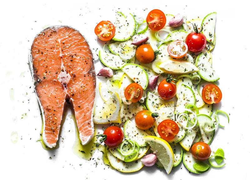 Ingredientes para cozinhar o almoço saudável - salmões e vegetais Peixes vermelhos, abobrinha, polpa, tomates de cereja, alho-por fotografia de stock royalty free