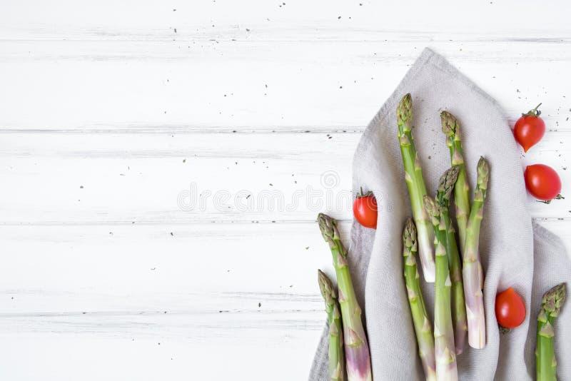 Ingredientes para cozinhar o café da manhã saudável: aspargo fresco, tomates na tabela branca Composição rústica do estilo Config fotografia de stock royalty free