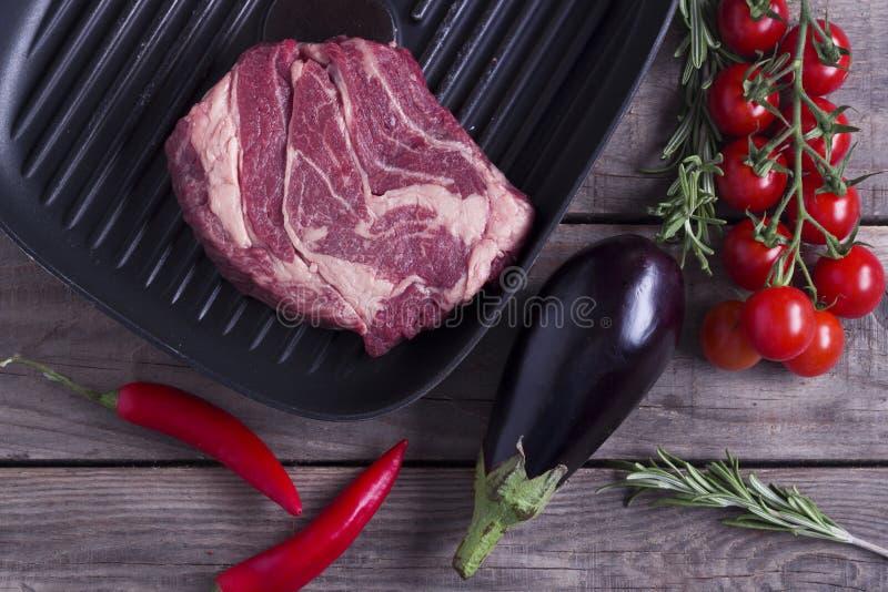 Ingredientes para cozinhar o jantar saudável da carne Bife cru cru na bandeja da grade do ferro com os vegetais sobre de madeira foto de stock royalty free