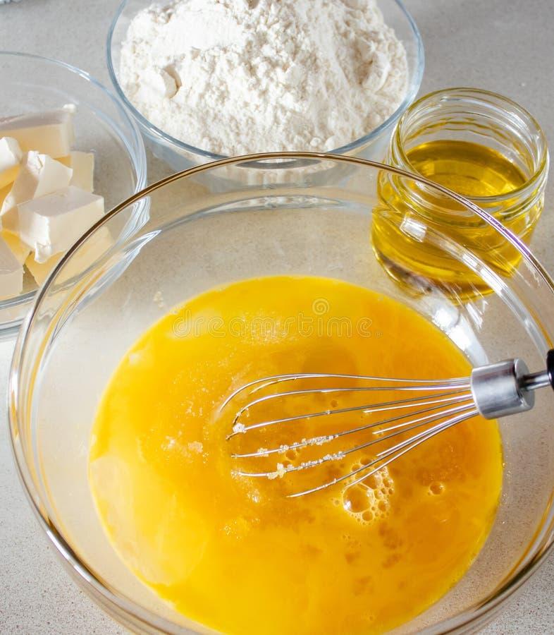 Ingredientes para cozinhar Ovos em uma bacia com um batedor de ovos para bater imagem de stock royalty free