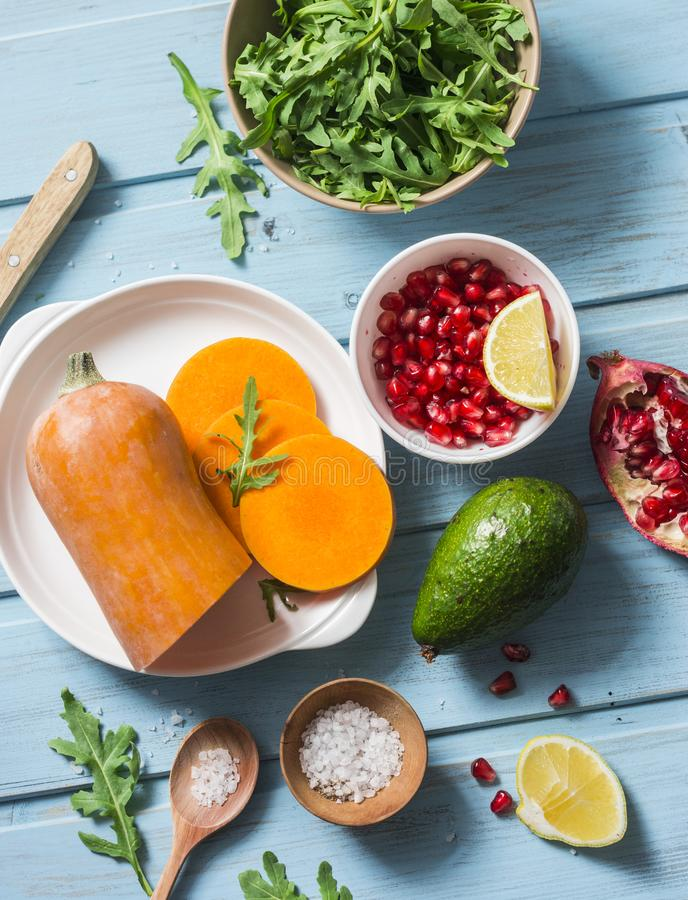 Ingredientes para cozinhar a polpa de butternut grelhada, rúcula e salada em uma tabela de madeira azul, vista superior da romã L imagem de stock royalty free