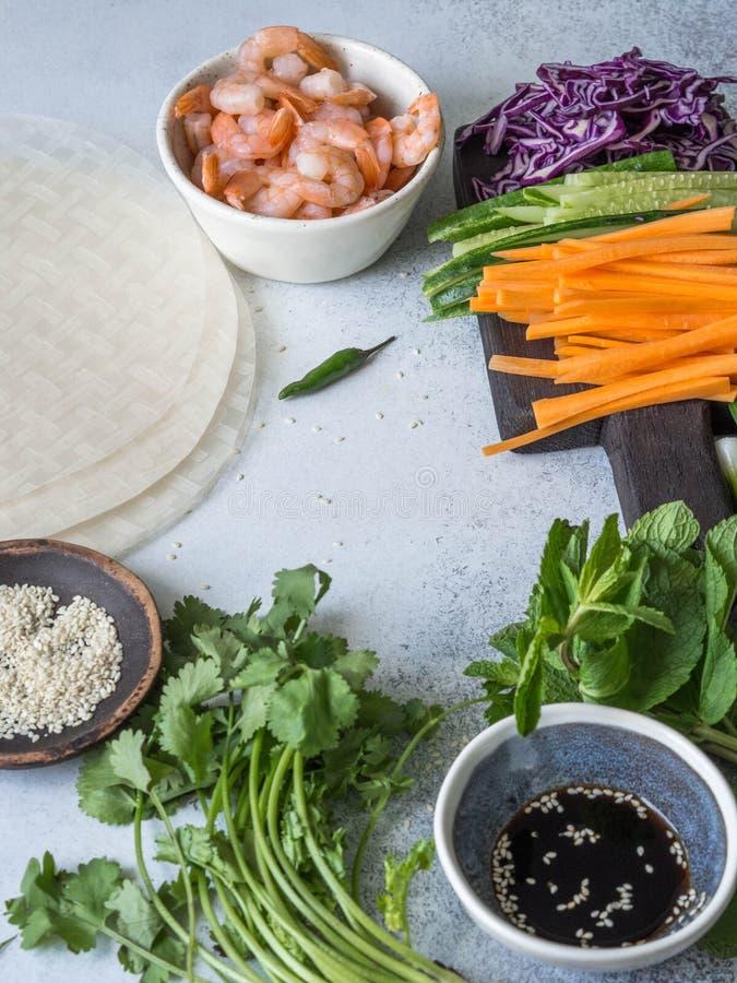 Ingredientes para cozinhar rolos de mola - cenouras, pepinos, ervas, couve vermelha, camarões, papel de arroz em um fundo cinzent imagens de stock royalty free