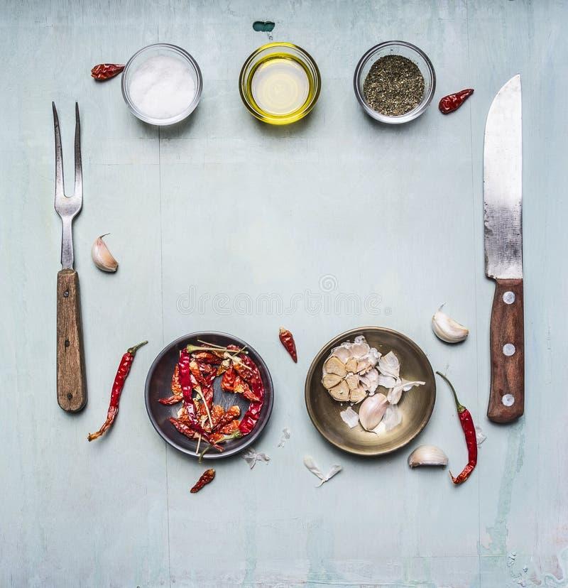 Ingredientes para cozinhar, temperando, óleo, faca, forquilha, alho, pimenta vermelha quente, quadro alinhado em clo rústicos de  imagens de stock royalty free