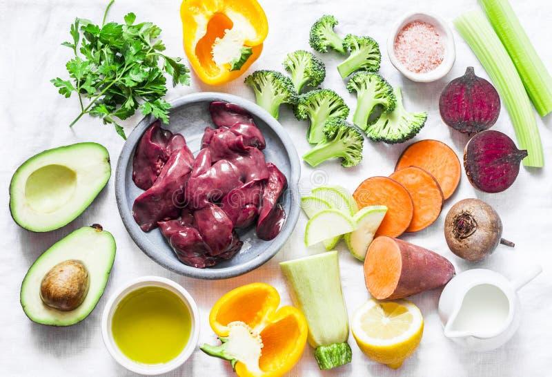Ingredientes para el almuerzo - hígado de pollo, patatas dulces, col del bróculi, paprikas, remolachas, habas, especias, aceite d foto de archivo libre de regalías
