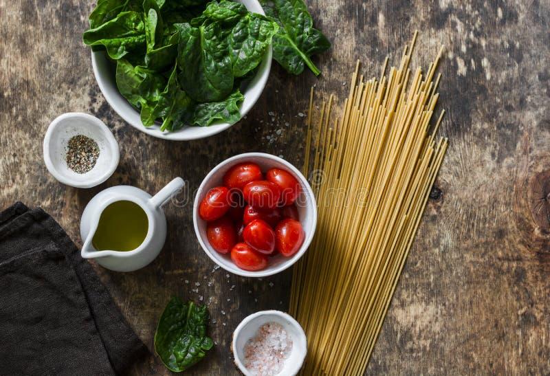 Ingredientes para el almuerzo sano vegetariano - pastas enteras de los espaguetis del grano, tomates de cereza, espinaca fresca e imagen de archivo