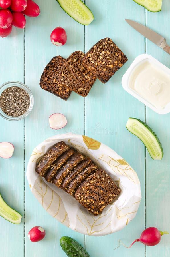 Ingredientes para el bocadillo del vegano con el queso cremoso, las semillas frescas del pepino, del rábano y del chia en fondo d fotografía de archivo libre de regalías