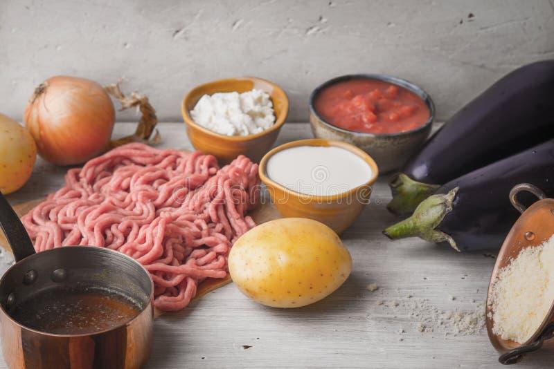 Ingredientes para el moussaka en la tabla de madera blanca horizontal foto de archivo