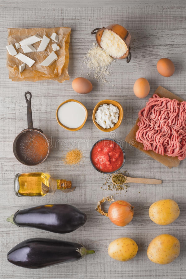 Ingredientes para el moussaka en la vertical blanca de la tabla imagen de archivo
