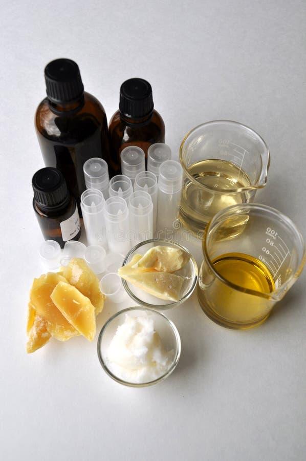 Ingredientes para fazer a manteiga natural do cacau dos cosméticos, o coco, a amêndoa, o jojoba e óleos essenciais com tubos e ga imagem de stock royalty free