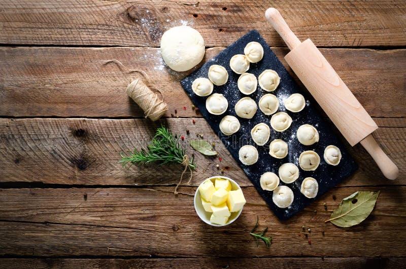 Ingredientes para fazer o pelmeni, ravioli, bolinhas de massa - massa, alecrim, pino do rolo, linha da lona, manteiga, folha de l fotos de stock royalty free