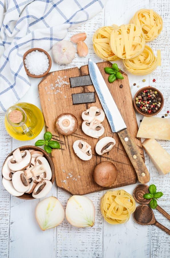 Ingredientes para hacer las pastas de los tallarines con las setas Alimento italiano sano imagen de archivo libre de regalías