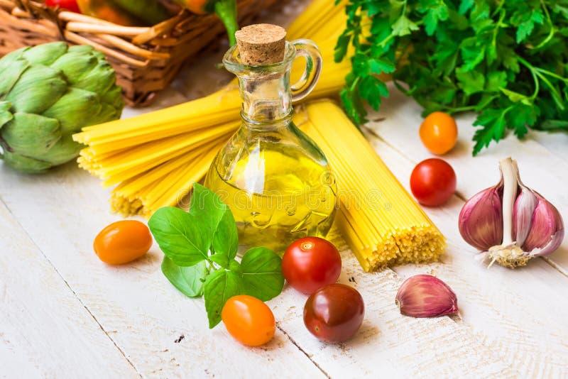Ingredientes para la cena italiana sana, espagueti, aceite de oliva, tomates de cereza, ajo, perejil, verduras en cesta fotografía de archivo libre de regalías