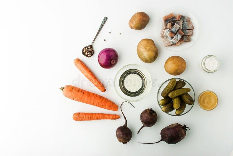 Ingredientes para la ensalada vegetal con la opinión superior de la remolacha y de los arenques imagenes de archivo