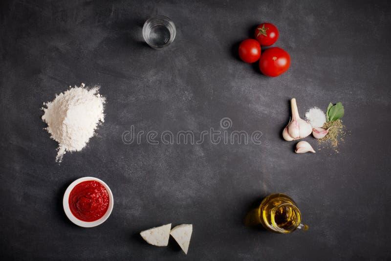 Ingredientes para la pizza en la pizarra imagenes de archivo