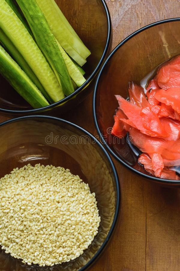 Ingredientes para la preparación del sushi en las placas en la tabla, que incluyen el jengibre conservado en vinagre, arroz, pepi foto de archivo libre de regalías
