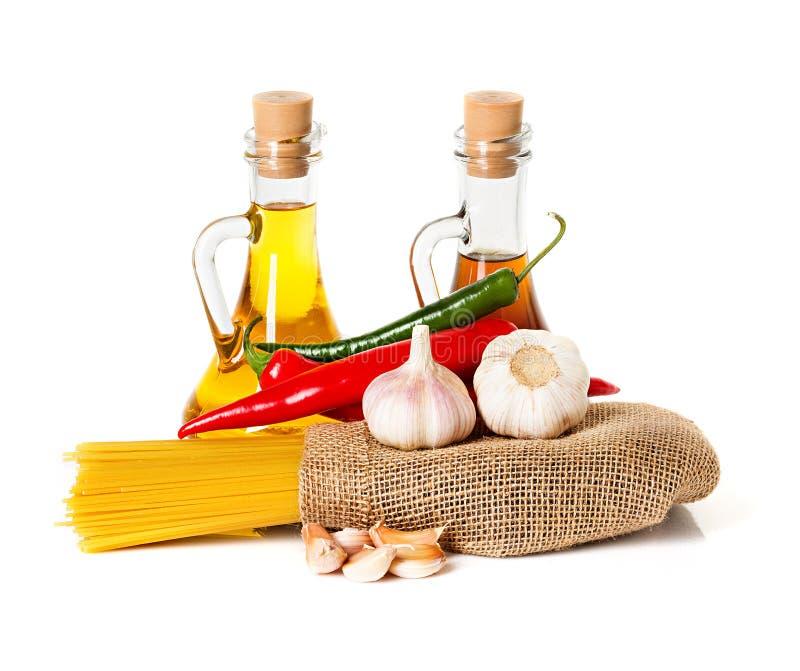 Ingredientes para las pastas. Espaguetis, chile, aceite, ajo imagen de archivo