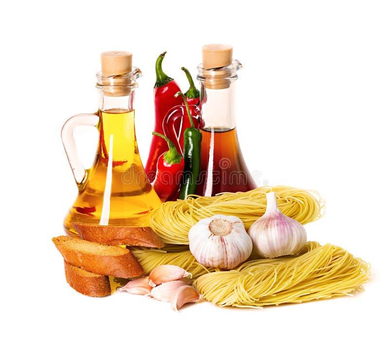 Ingredientes para las pastas. Espaguetis, chile, aceite, ajo foto de archivo